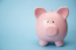 Piggy bank with copy space on blue background